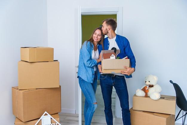 Jovem família feliz com caixas de papelão, abrindo a porta de sua nova casa e entrando no apartamento vazio.