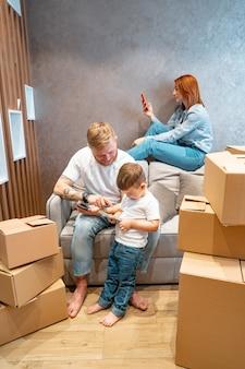 Jovem família feliz com criança desembalar caixas juntas, sentado no sofá