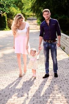 Jovem família feliz com um lindo bebê de olhos azuis andando no parque de verão ao pôr do sol