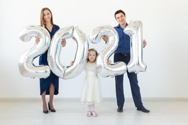 Jovem família feliz, mãe, pai e filha em pé perto de balões em forma de números 2021
