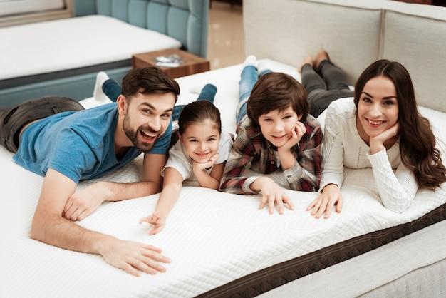 Jovem família feliz relaxante na cama macia na loja