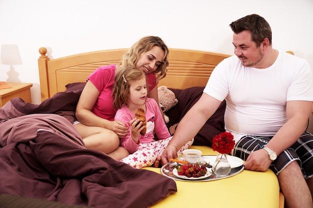 Jovem família feliz tomando café da manhã na cama