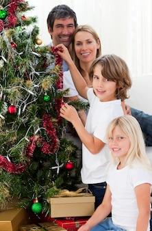 Jovem família que decora uma árvore de natal