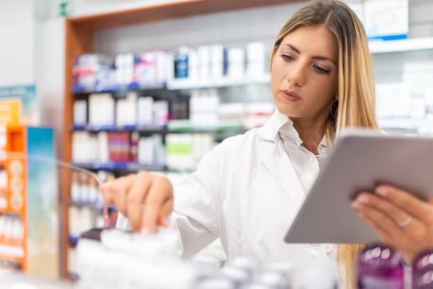 Jovem farmacêutica verificando o inventário em uma farmácia