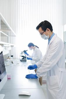 Jovem farmacêutico ou pesquisador chinês testando uma nova vacina enquanto seu colega estuda as características do vírus em segundo plano