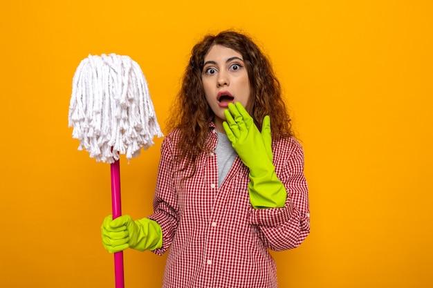 Jovem faxineira assustada usando luvas segurando um esfregão