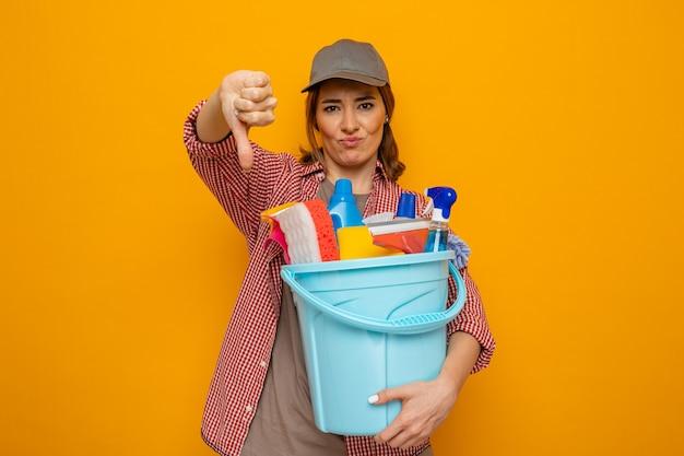 Jovem faxineira com camisa xadrez e boné segurando um balde com ferramentas de limpeza, olhando para a câmera descontente, mostrando os polegares para baixo em pé sobre um fundo laranja