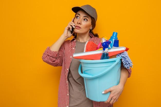 Jovem faxineira com camisa xadrez e boné segurando um balde com ferramentas de limpeza, olhando para o lado com uma expressão confiante enquanto fala no celular