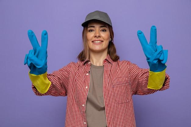 Jovem faxineira com camisa xadrez e boné usando luvas de borracha e sorrindo alegremente mostrando o sinal v