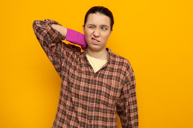 Jovem faxineira com camisa xadrez e luvas de borracha, parecendo cansada e exausta, tocando seu pescoço, sentindo dor em pé sobre a parede laranja
