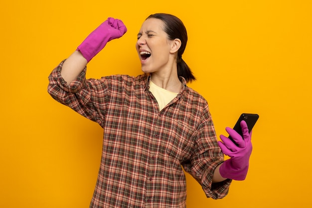 Jovem faxineira com camisa xadrez e luvas de borracha segurando o smartphone feliz e animada, levantando o punho em pé na laranja