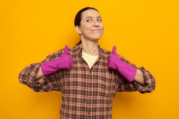 Jovem faxineira com roupas casuais e luvas de borracha, olhando para o lado com um sorriso no rosto feliz, mostrando os polegares em pé sobre a parede laranja