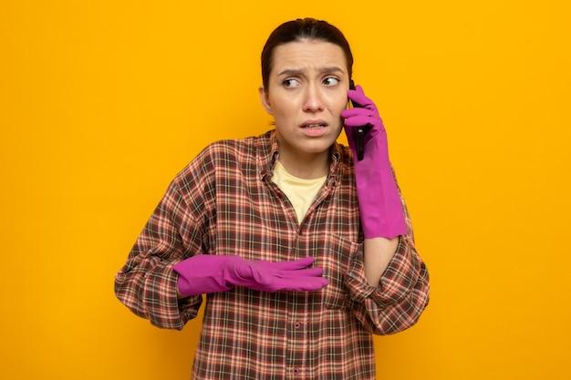 Jovem faxineira com roupas casuais e luvas de borracha, parecendo confusa enquanto fala no celular, em pé sobre a parede laranja