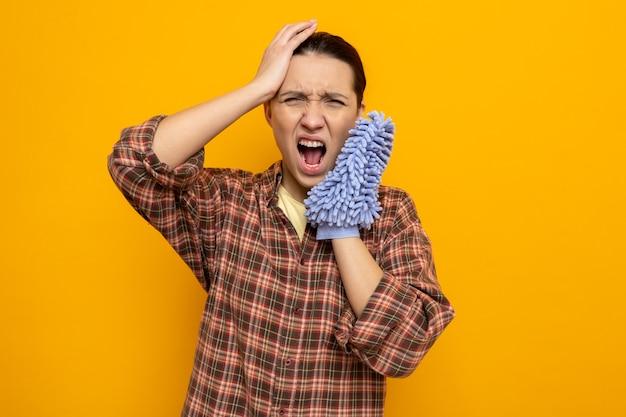 Jovem faxineira com roupas casuais segurando espanador, gritando com uma expressão irritada e frustrada em pé sobre a parede laranja