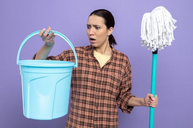 Jovem faxineira com roupas casuais, segurando um esfregão e um balde, olhando para ela surpresa e confusa em pé sobre a parede roxa