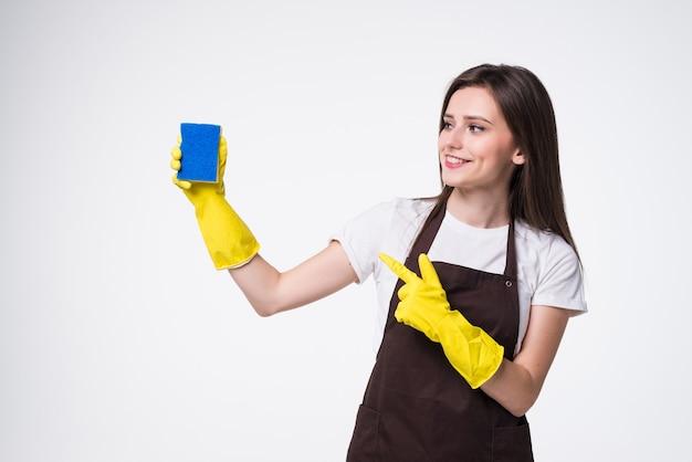 Jovem faxineira em pé segurando uma esponja
