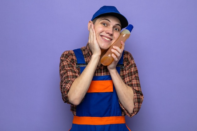 Jovem faxineiro de uniforme e boné segurando agente de limpeza isolado na parede azul