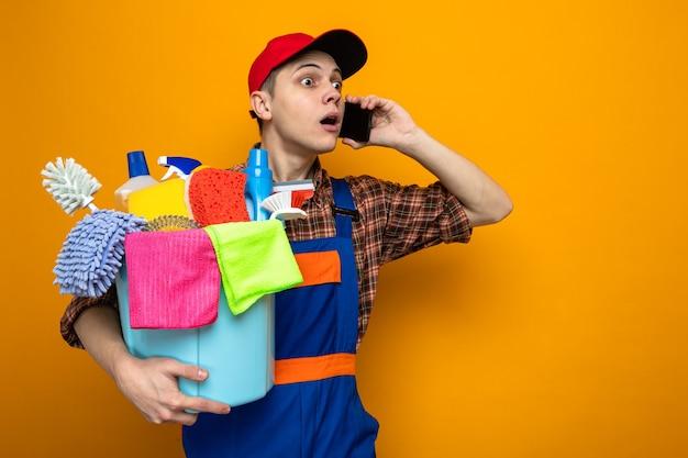 Jovem faxineiro de uniforme e boné segurando balde de ferramentas de limpeza fala no telefone isolado na parede laranja