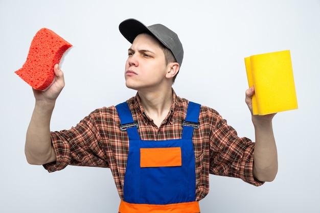 Jovem faxineiro de uniforme e boné segurando e olhando para esponjas isoladas na parede branca