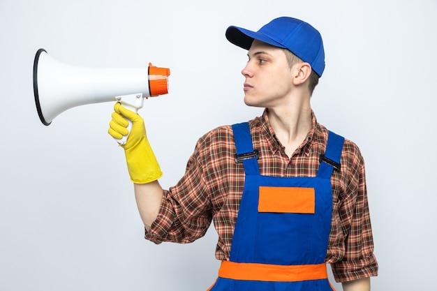 Jovem faxineiro usando uniforme e boné com luvas fala no alto-falante isolado na parede branca