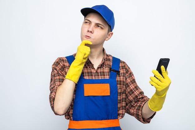 Jovem faxineiro usando uniforme e boné com luvas segurando o telefone isolado na parede branca