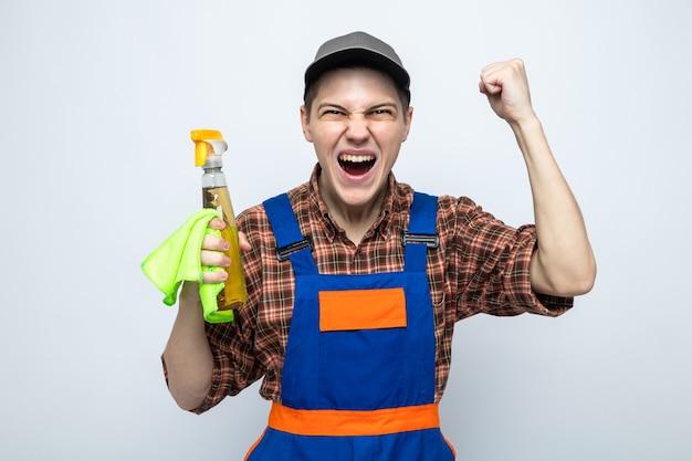Jovem faxineiro usando uniforme e boné segurando um pano com agente de limpeza isolado na parede branca