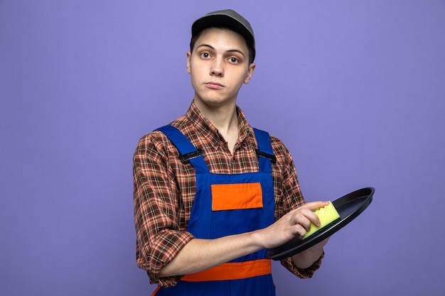 Jovem faxineiro vestindo uniforme e boné com uma esponja isolada na parede roxa