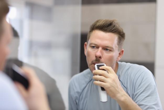 Jovem faz a barba com navalha em frente ao espelho Foto Premium