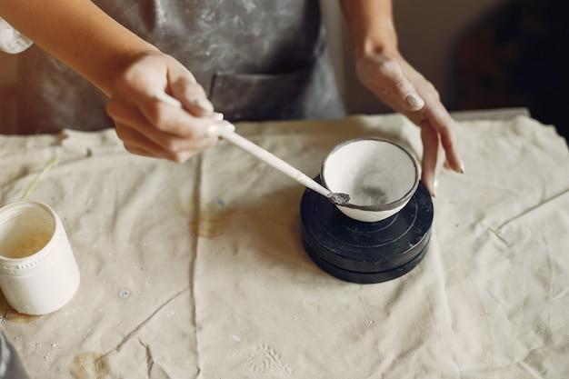 Jovem faz cerâmica na oficina