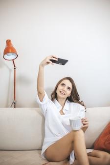 Jovem faz selfie sentado no sofá em casa. jovem bebe café em caneca grande e usa smartphone