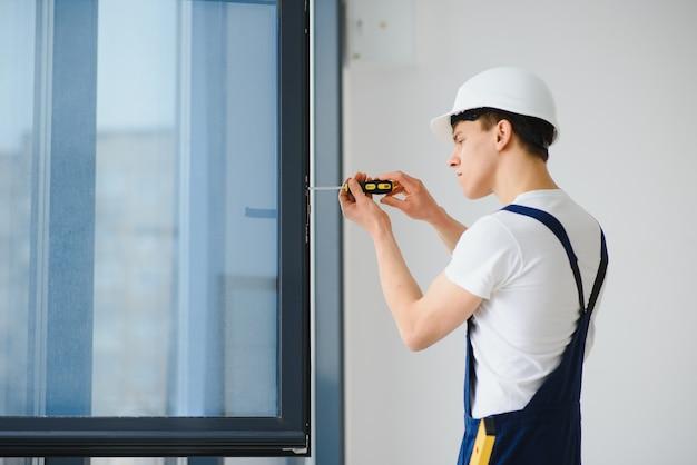 Jovem faz-tudo consertando janela com chave de fenda