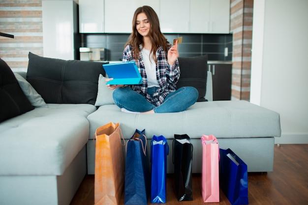 Jovem faz uma compra em casa em um tablet pc. no site de vendas, ela fará muitas compras enquanto está sentada em casa no sofá.