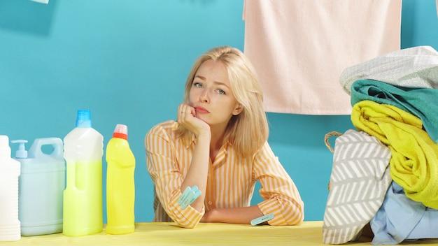 Jovem faz uma pausa na lavagem e limpeza enquanto está sentado em uma mesa em uma parede azul isolada