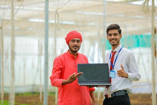 Jovem fazendeiro e agrônomo indiano aparecendo com um laptop na estufa
