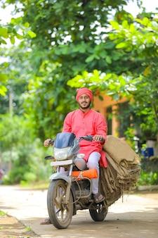 Jovem fazendeiro indiano coleta bolsa de saco em moto