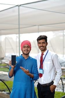 Jovem fazendeiro indiano com agrônomo mostrando telefone inteligente em casa polivalente ou estufa