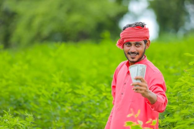 Jovem fazendeiro indiano com dinheiro no campo