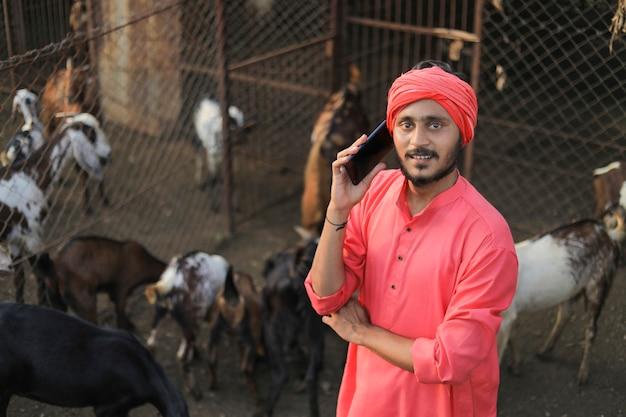 Jovem fazendeiro indiano com smartphone em fazenda de gado leiteiro