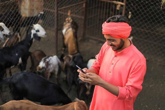 Jovem fazendeiro indiano com smartphone em fazenda de gado leiteiro Foto Premium