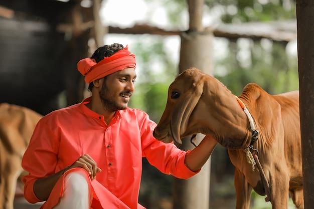 Jovem fazendeiro indiano com sua vaca na fazenda