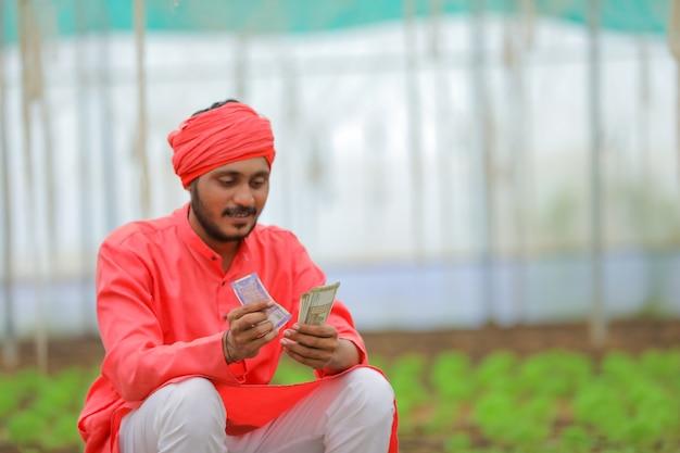 Jovem fazendeiro indiano contando dinheiro em uma estufa ou casa polivalente