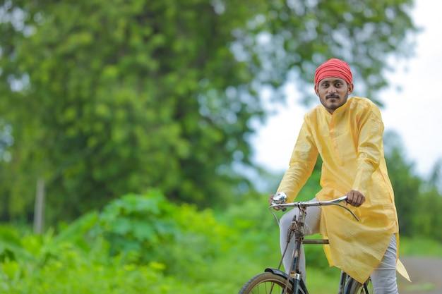 Jovem fazendeiro indiano e seu filho indo para a escola de bicicleta