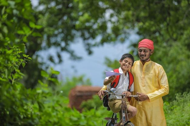 Jovem fazendeiro indiano e seu filho indo para a escola