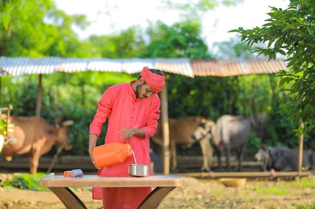 Jovem fazendeiro indiano em fazenda de gado leiteiro