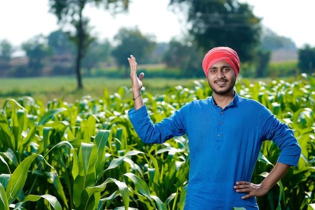 Jovem fazendeiro indiano em uma plantação de milho