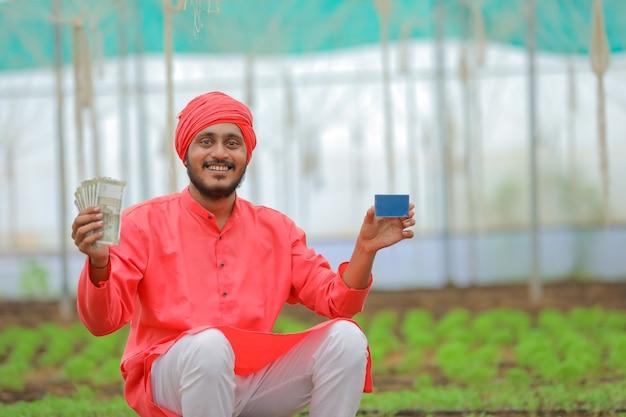Jovem fazendeiro indiano mostrando dinheiro e cartão em branco na estufa