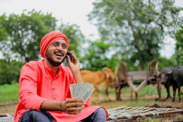 Jovem fazendeiro indiano mostrando dinheiro e falando no celular em casa