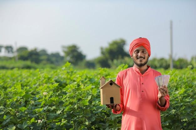 Jovem fazendeiro indiano mostrando dinheiro no campo