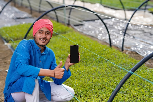 Jovem fazendeiro indiano mostrando telefone inteligente em casa poli ou estufa