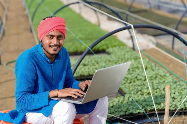Jovem fazendeiro indiano usando laptop em uma estufa ou casa poli